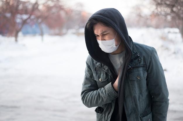 Vista frontal del hombre enfermo con una máscara médica