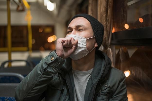 Vista frontal del hombre enfermo tosiendo en el autobús mientras usa una máscara médica