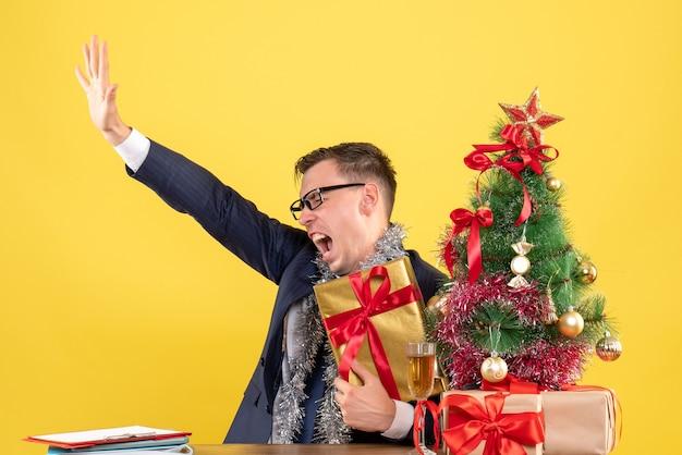 Vista frontal del hombre enojado abriendo la mano sentada en la mesa cerca del árbol de navidad y presenta en la pared amarilla