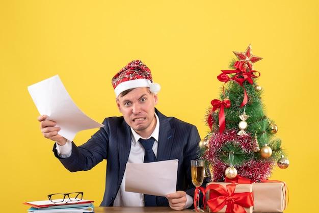 Vista frontal hombre enojado con gorro de papá noel sentado en la mesa cerca del árbol de navidad y presenta sobre fondo amarillo