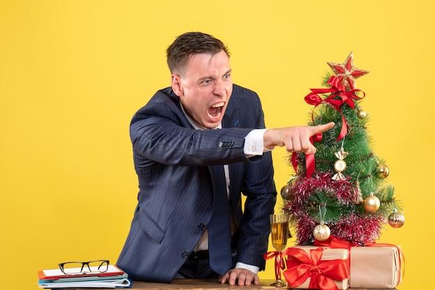 Vista frontal hombre enojado gritando a alguien de pie detrás de la mesa cerca del árbol de navidad y presenta sobre fondo amarillo