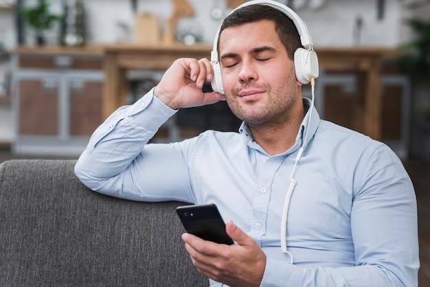 Vista frontal del hombre escuchando música