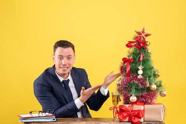 Vista frontal del hombre feliz apuntando al árbol de navidad sentado en la mesa cerca del árbol de navidad y regalos en amarillo