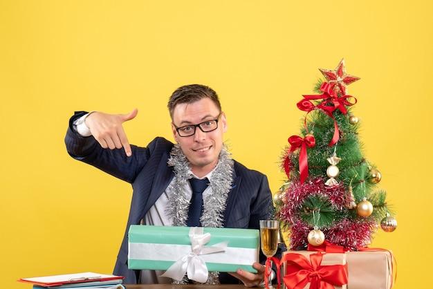 Vista frontal del hombre feliz apuntando al regalo sentado en la mesa cerca del árbol de navidad y presenta en amarillo