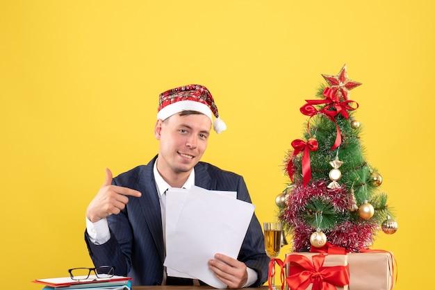 Vista frontal del hombre feliz apuntando a los documentos sentado en la mesa cerca del árbol de navidad y presenta en amarillo