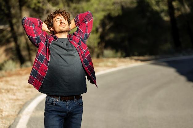 Vista frontal del hombre feliz disfrutando de la naturaleza durante un viaje por carretera con espacio de copia