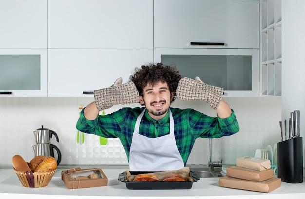 Vista frontal del hombre feliz vestido con soporte de pie detrás de la mesa con pasteles recién horneados en la cocina blanca