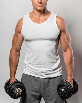 Vista frontal del hombre en forma con camiseta sin mangas y pesas