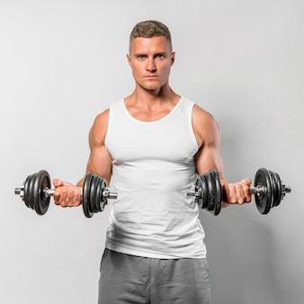 Vista frontal del hombre en forma con camiseta sin mangas con pesas