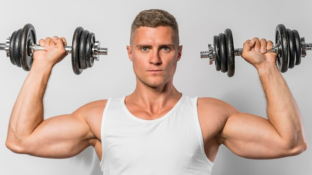 Vista frontal del hombre en forma con camiseta sin mangas sosteniendo pesas