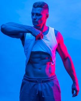Vista frontal del hombre en forma posando mientras levanta la camiseta sin mangas