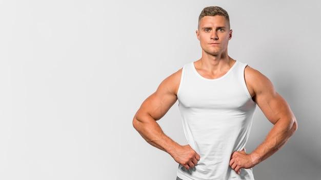 Vista frontal del hombre en forma posando mientras usa camiseta sin mangas con espacio de copia