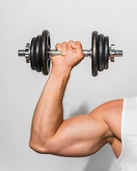 Vista frontal del hombre en forma sosteniendo pesas