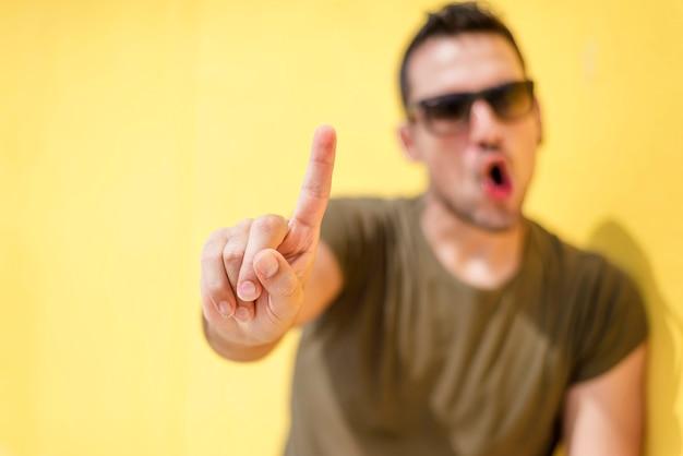 Vista frontal de un hombre fresco desenfoque diciendo que no con gafas de sol contra una pared amarilla