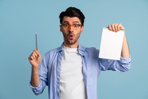 Vista frontal del hombre con gafas que tiene una idea mientras sostiene el cuaderno y la pluma