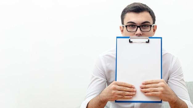 Vista frontal del hombre con gafas sosteniendo el bloc de notas con espacio de copia
