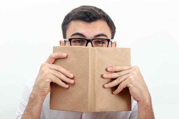 Vista frontal del hombre con gafas y sosteniendo el libro cerca de la cara