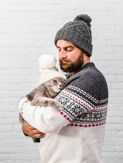 Vista frontal hombre y gatito con gorro de piel