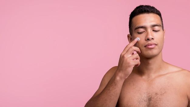 Vista frontal del hombre guapo aplicando crema facial con espacio de copia