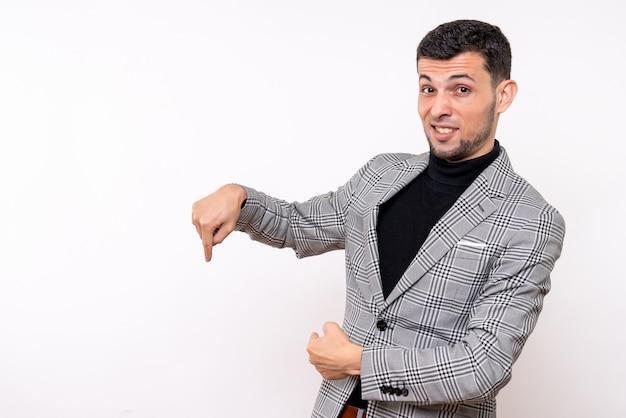 Vista frontal hombre guapo en traje apuntando al piso de pie sobre fondo blanco aislado