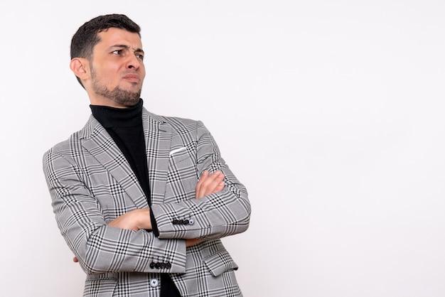 Vista frontal hombre guapo en traje cruzando las manos de pie sobre fondo blanco aislado