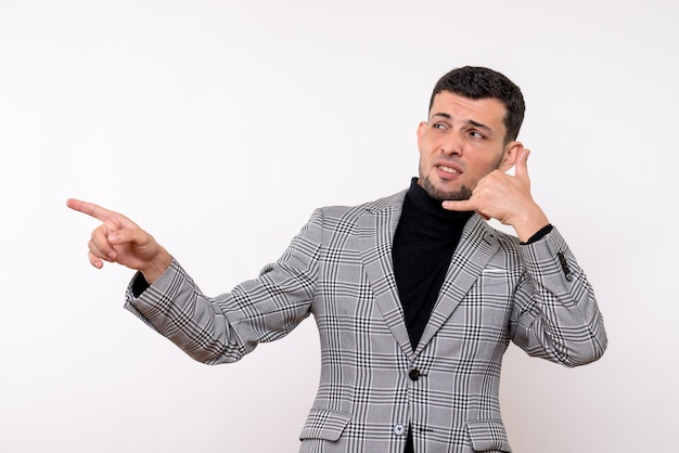 Vista frontal hombre guapo en traje haciendo gesto de llamarme teléfono de pie sobre fondo blanco aislado