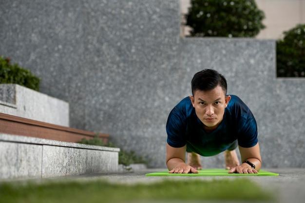 Vista frontal del hombre haciendo yoga en la estera junto a los pasos