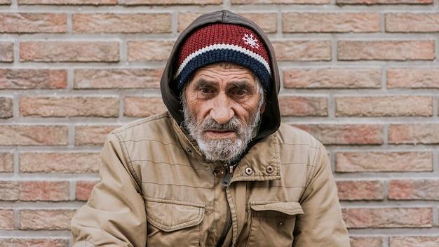 Vista frontal del hombre sin hogar delante de la pared
