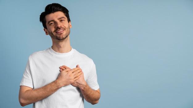 Vista frontal del hombre impresionado tocando su corazón con las manos