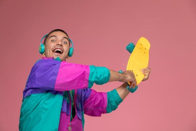 Vista frontal del hombre joven en abrigo colorido sosteniendo patineta sobre fondo rosa
