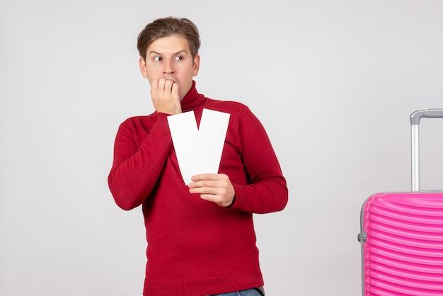 Vista frontal del hombre joven con billetes de avión asustado sobre fondo blanco.