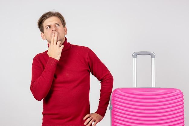 Vista frontal del hombre joven con bolsa rosa pensando sobre fondo blanco.