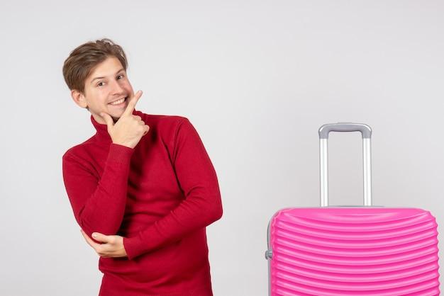 Vista frontal del hombre joven con bolsa rosa posando sobre fondo blanco.