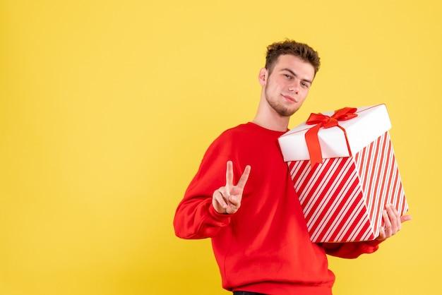Vista frontal del hombre joven en camisa roja con regalo de navidad