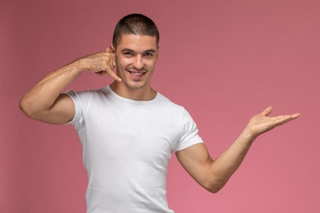 Vista frontal hombre joven en camiseta blanca posando mostrando llamada telefónica sobre fondo rosa