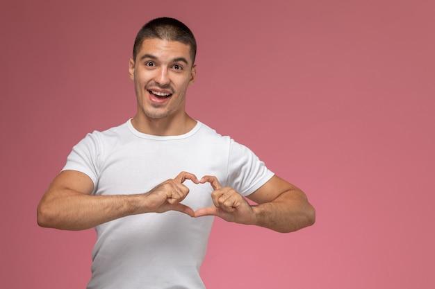 Vista frontal del hombre joven en camiseta blanca que muestra el signo del corazón sobre fondo rosa