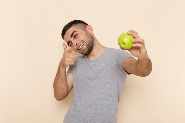 Vista frontal del hombre joven en camiseta gris y jeans azules sonriendo y sosteniendo manzana verde en beige