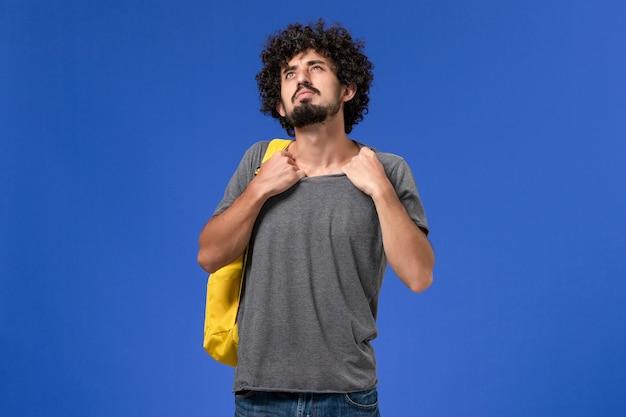 Vista frontal del hombre joven en camiseta gris con mochila amarilla arrancando su camisa en la pared azul claro
