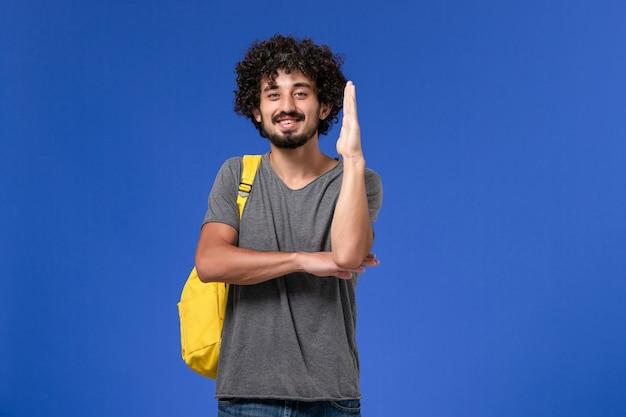 Vista frontal del hombre joven en camiseta gris con mochila amarilla levantando su mano sobre la pared azul