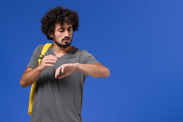 Vista frontal del hombre joven en camiseta gris con mochila amarilla mirando su muñeca en la pared azul