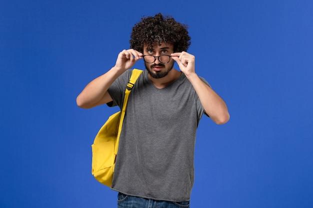 Vista frontal del hombre joven en camiseta gris con mochila amarilla en la pared azul