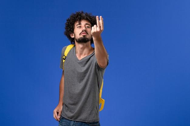 Vista frontal del hombre joven en camiseta gris con mochila amarilla posando en la pared azul