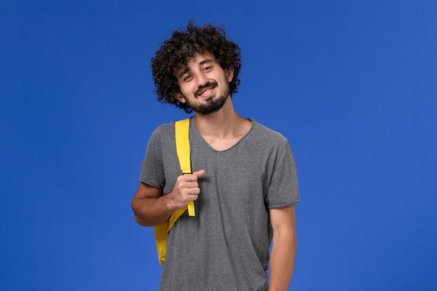 Vista frontal del hombre joven en camiseta gris con mochila amarilla sonriendo en la pared azul