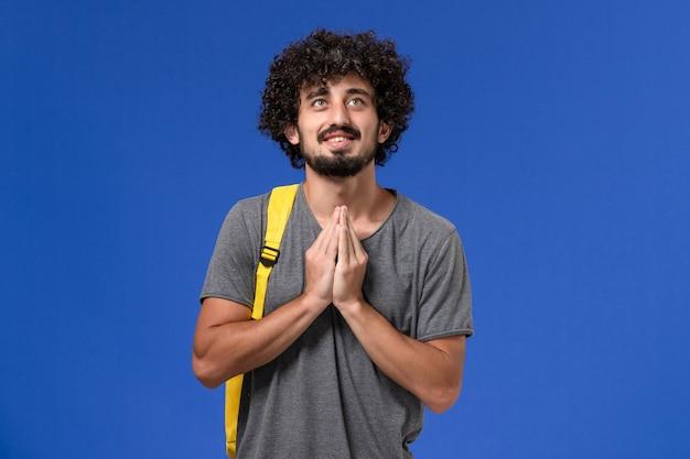 Vista frontal del hombre joven en camiseta gris con mochila amarilla sonriendo y rezando en la pared azul