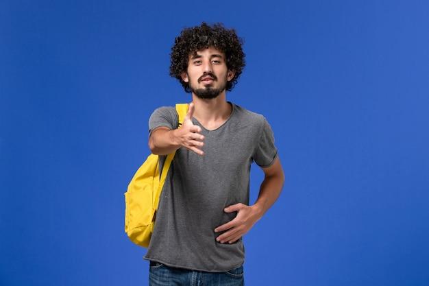 Vista frontal del hombre joven en camiseta gris con mochila amarilla tratando de estrechar la mano en la pared azul