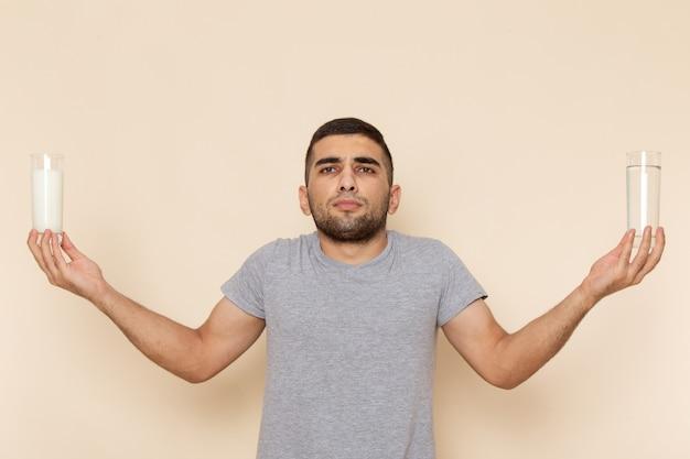 Vista frontal hombre joven en camiseta gris con vaso de agua, leche en beige