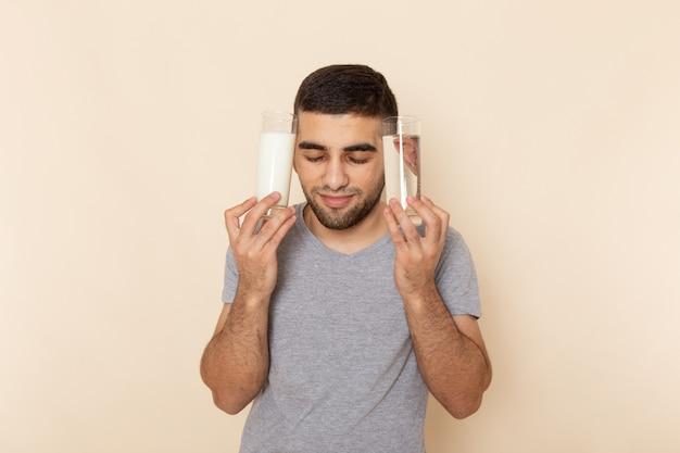 Vista frontal del hombre joven en camiseta gris con vasos de agua, leche en beige