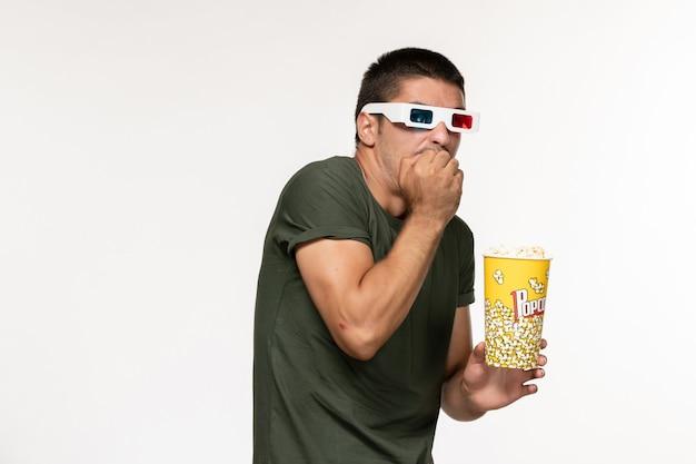 Vista frontal hombre joven en camiseta verde con palomitas de maíz en gafas de sol d viendo la película en la pared blanca película película masculina de cine solitario