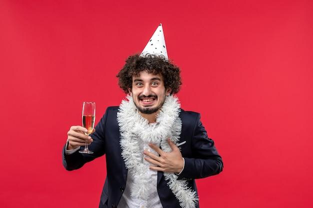 Vista frontal del hombre joven celebrando el año nuevo que viene en la pared roja navidad humana de vacaciones