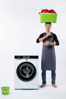 Vista frontal del hombre joven doblando ropa sucia en la pared blanca